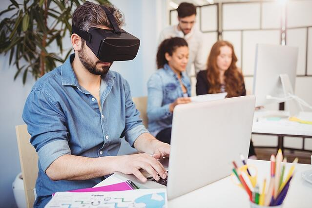 Businessman wearing virtual reality headset while using laptop against colleagues in creative office.jpeg