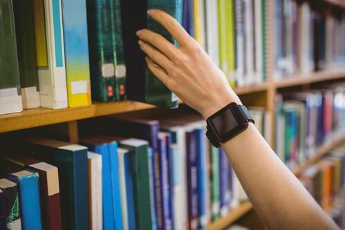 Student picking book in library wearing smart watch at the university.jpeg